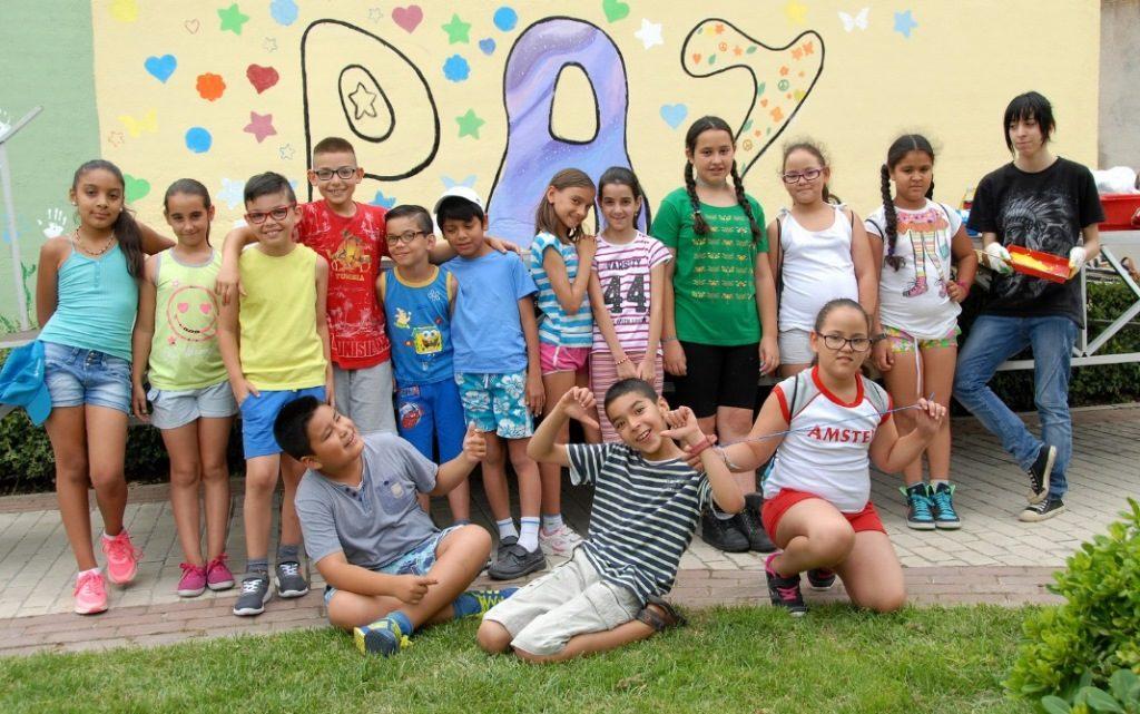 """Alumnos que pasan el verano en los campamentos de La Morada, y que han contribuido a la creación del """"Mural de la paz""""."""